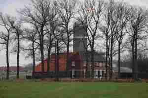 Tussen de bomen het oude Mallemse gewaarde erve Roossink. Oorspronkelijk een goed van het Stift Vreden, rond 1600 een bezit van de Provisorie van de Stad Eibergen, en in het midden van de 19de eeuw door de burgerlijke gemeente overgedaan aan de Hervormde Diaconie van Eibergen. Op de achtergrond de Watertoren midden op de Mallemse Es. Linksachter het erve Slotman, dat in het markenboek nog als keuter wordt betiteld. Er voorlangs loopt de N18 of Twenteroute.